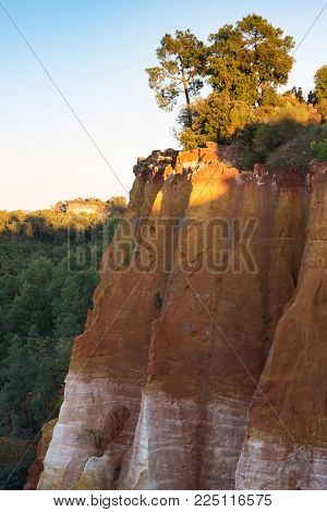 Dramatic Ochre Cliffs Topped With Lush Vegetation Photographed In Roussillon France At Sunset.