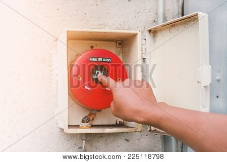 Hand pressing fire alarm to warn people that there is a fire in the building for safety in work and industrial concept