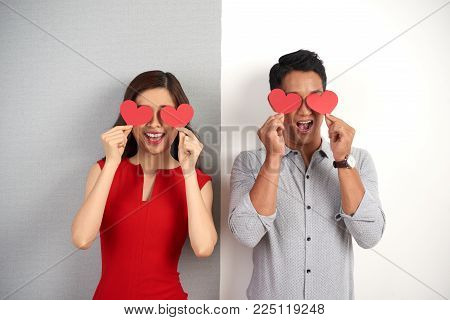 Cheerful young couple standing against gray and white background and covering their eyes with heart shaped pieces of paper, group portrait