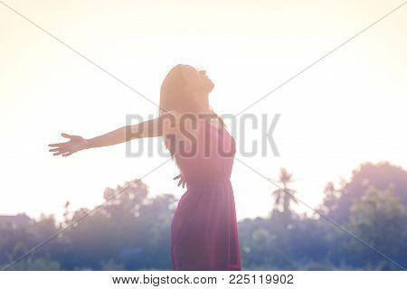 Young beauty woman happy relaxing smile with sunglasses and pink dress cloth in summer sunset sky outdoor. People freedom style.