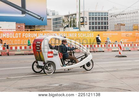 Berlin, October 1, 2017: Unknown Elderly Bike Taxi Driver Carries Passenger On Road Past People And