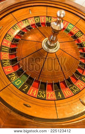 Round, wooden roulette wheel with numbers in a circle of a yellow wheel