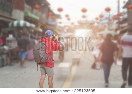 Beautiful woman traveler holding camera in hands.Traditional being sold at chinese chinatown outdoor market.