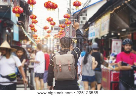 Man tourist walking in chinatown on china travel. Asian handsome man on food street during Asia summer vacation.Traditional being sold at chinese chinatown outdoor market.