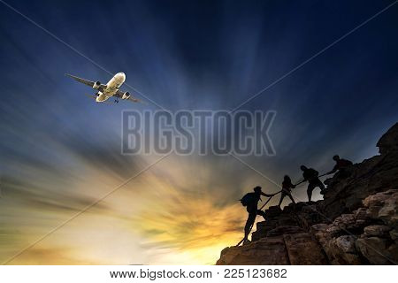 Group of hikers climbing up mountain cliff and one of them giving helping hand. People helping and, team work concept.