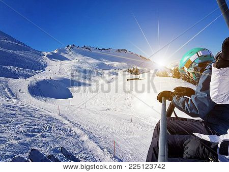 Woman skier sitting downhill during sunny day in high mountains.