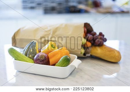 Colorful fresh vegetables and fruits with a bag of groceries shopping in the kitchen.Healthy eating concept