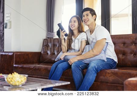 Happy asian young couple loving on the couch watching a movie together,Woman holding remote and her husband sittind next to her.