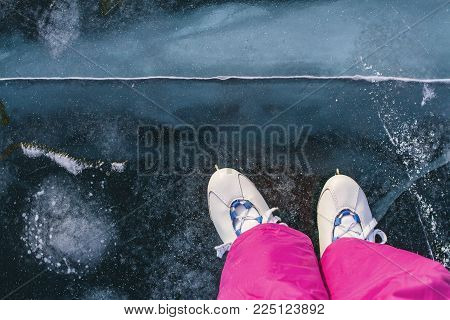 A girl skater in vintage skates and pink ski pants skates on the beautiful fairy blue clear ice of Lake Baikal with cracks and snow.