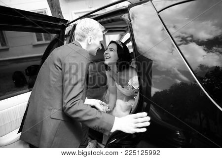 black-and-white photo .happy couple talking near wedding limo.holidays and events