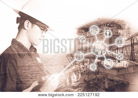 Double exposure of Engineer or Technician man with digital icon operated platform or plant by using tablet with offshore oil and gas platform background for industry business concept.