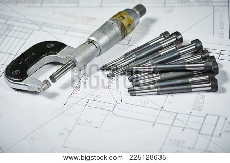metalworking industry and machining. Details with measuring micrometer on print drawing