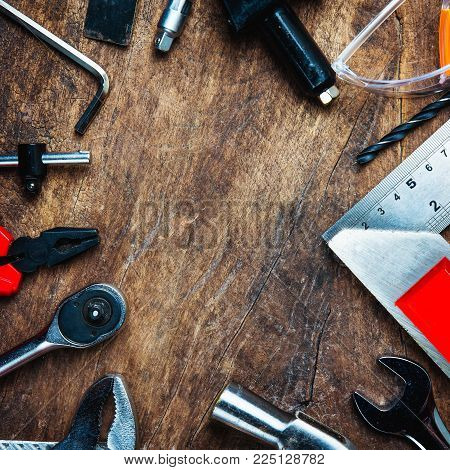 Set of construction tools on wooden board as wrench, hammer, pliers, socket wrench, spanner, tape measure, electric drill,safety glasses, screwdriver.