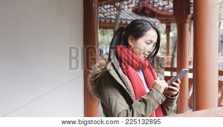 Woman surf the internet and sitting inside Chinese pavilion, woman wearing winter jacket