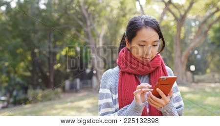 Woman looking at mobile phone in park