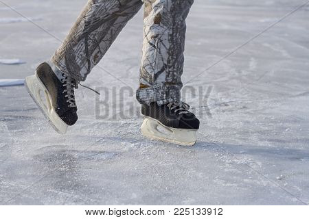 A skater in winter warm trousers beautifully rolls in ice skates on the ice of Lake Baikal in winter.