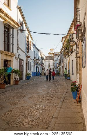 Cordoba, Spain - April 10, 2017: Old typical street in the Alcazar Viejo quarter of Cordoba with white walls decorated with flowers. This quarter is famous for his decorated with flowers courtyards.