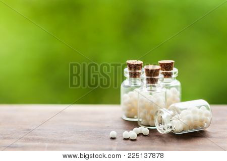 Classical Homeopathy globules in vintage bottles and nature leaves