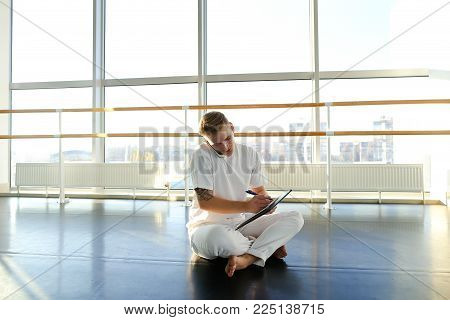Fitness trainer discussing details with new client on smartphone in gym, handsome guy sitting on parquet floor with planchette in hands and talking on mobile. Male wearing sport clothes in spacious light well-equipped hall with big windows.