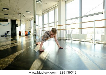 Faculty of physical education student diligently push up, handsome guy in white trousers doing gymnastic exercises. Tattooed male in well-equipped light spacious university hall. Concept of man sportswear, individual trainings or workouts in big gym
