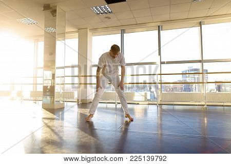 Architect spill out energy in gym, fair-haired guy waving hands hoping. Energetic tattooed boy with mustache wearing white T-shirt and trousers. Concept of man sportswear, big well-equipped hall or individual trainings.
