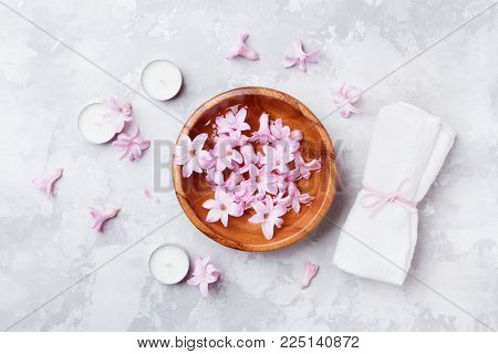Aromatherapy, beauty and spa background with perfumed pink flowers water in wooden bowl and candles on stone table. Top view, flat lay.