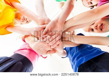 Indoor studio children's hands, close-up view, hands holding together as a team