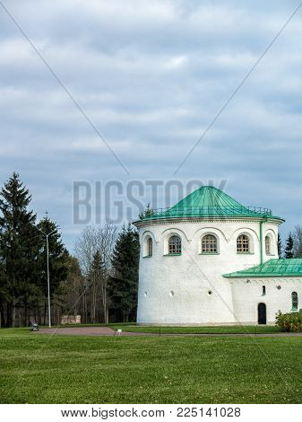 Part of the architectural complex Ratnaya Chamber in Tsarskoe Selo in the Alexander Park with a lawn, a bench, a path, a forest in cloudy weather in the autumn. Saint-Petersburg, Russia