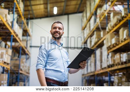 Portrait of a male warehouse worker or a supervisor holding notes.