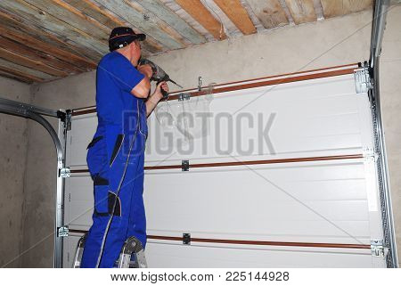 Kyiv, Ukraine - February, 12, 2018: Contractor Installing Garage Door And Drilling Hole For Garage D