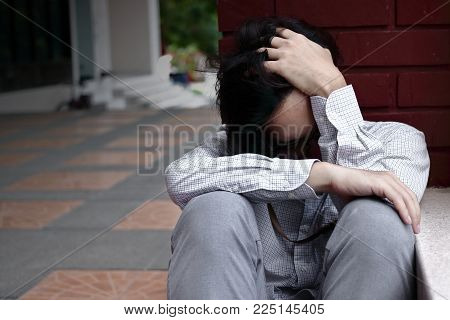 Frustrated stressed young Asian business man feeling disappointed or exhausted with job at outside office.