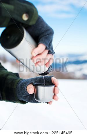 Man using thermos bottle on the snowy mountain