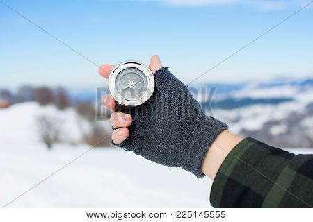 Man holding a metal compass on snowy mountain