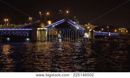 Opening drawbridge. Bridge over the river, illuminating the water with light from lampposts. City night scene with illuminated bridge over river.Saint Petersburg, Russia.