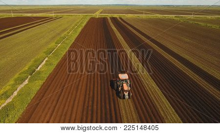 Farmer in tractor preparing land with seedbed cultivator in farmlands. Tractor plows a field. Agricultural work in processing, cultivation of land. Farmers preparing land and fertilizing. Agricultural workers with tractors.