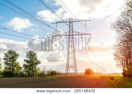 Beatiful Sunset Above The Modern High Powerlines On The Field