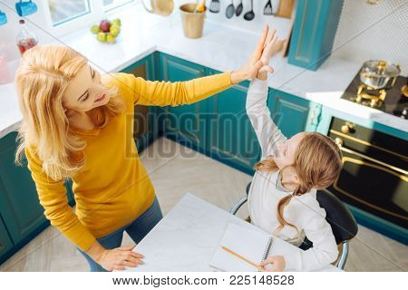 Good day. Good-looking joyful blond slim mother smiling and doing a high-five with her daughter sitting at the table