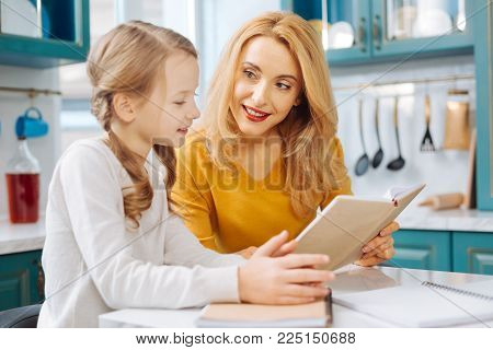 Happy mother. Pretty alert blond slim mother smiling and looking at her daughter and while sitting at the table and her daughter reading