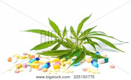 Marijuana leafs with colorful medical pills isolated