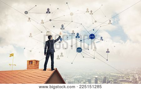 Young man standing with back on roof and drawing connection lines. Mixed media