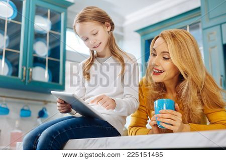 My dear family. Good-looking happy fair-haired slim mother smiling and holding a cup of tea while her daughter using a tablet while sitting on the table