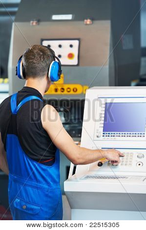 worker at workshop operating punch press machine tool by computer