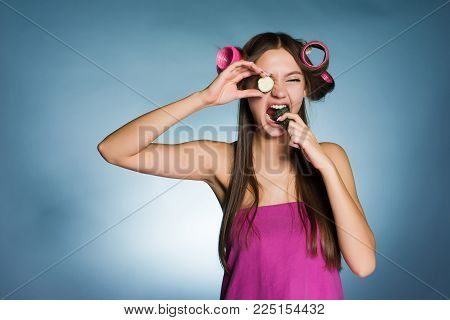 woman with curlers on her head eating a cucumber on a blue background