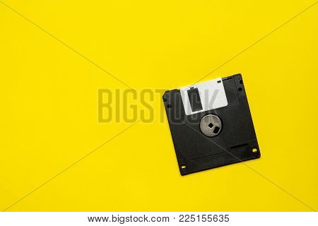 floppy data storage diskette on yellow background with copy space.