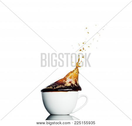 cup of spilling coffee creating splash isolated on white background.