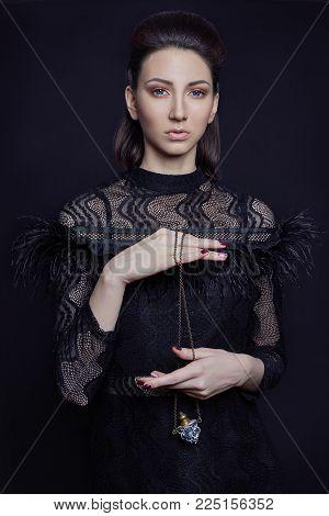 Contrast Fashion Armenian Woman Portrait With Big Blue Eyes On A Dark Background In A Purple Dress.