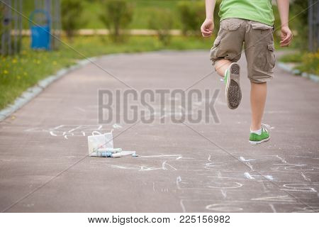 Closeup of hopscotch drawn with chalk on asphalt road and jumping boy. Children games and outdoor activities.