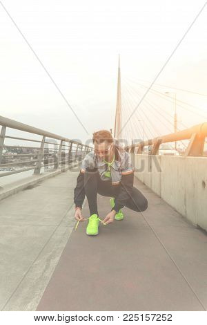Male Jogger Tying Shoelace On A Big Bridge.