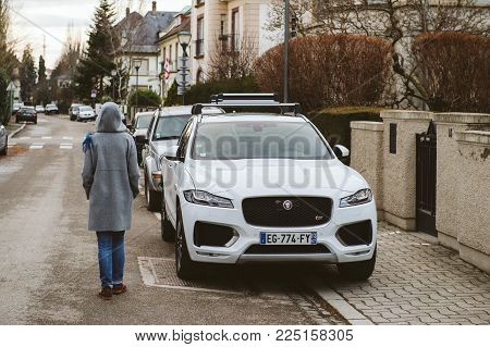 Strasbourg, France - Jan 15, 2017: Rear View Of Woman Walking On The Street Next To Luxury Jaguar Su