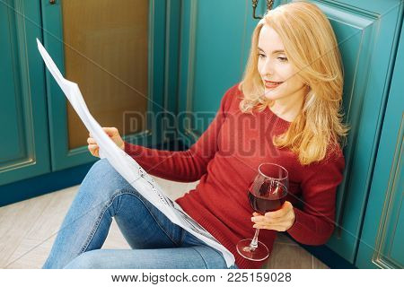 Relaxing at home. Pretty inspired fair-haired young woman smiling and reading a newspaper and holding g a glass of good red wine while sitting on the floor